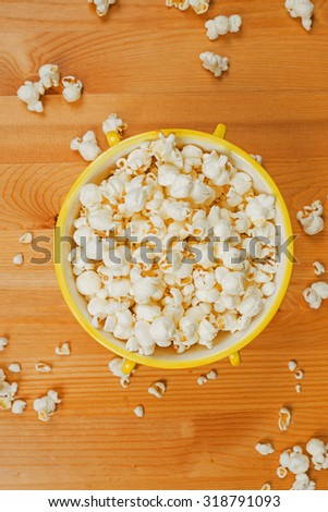 A bowl of popcorn on a wooden table