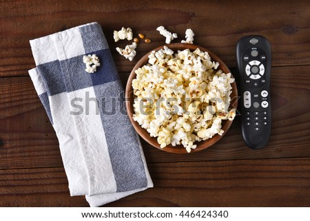 A bowl of popcorn, towel and a TV remote on a rustic wood table