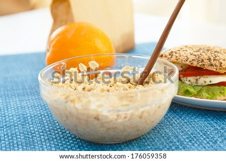 A bowl of porridge and a sandwich with an orange - stock photo