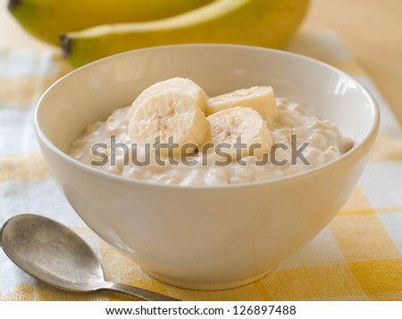 A bowl of porridge with bananas, selective focus - stock photo