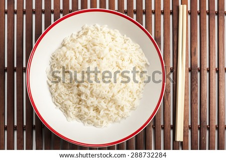 a bowl of rice on a bamboo mat - stock photo
