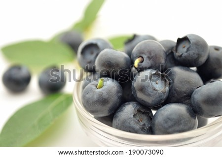 A bowl of ripe blueberries with some on the side. - stock photo