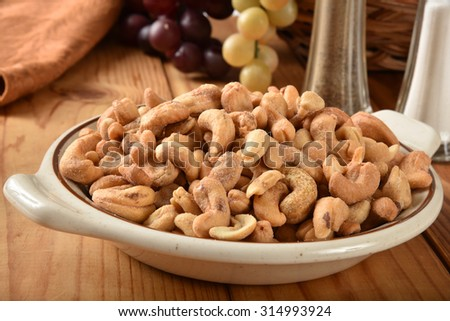 A bowl of roasted salted cashews on a rustic table - stock photo