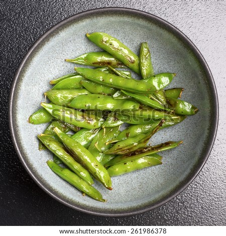 A bowl of roasted sugar snap peas photographed from directly above.