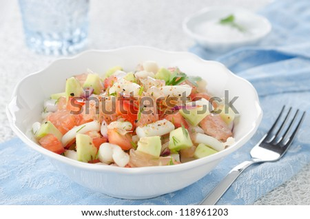 A bowl of salad with squid, avocado and grapefruit, closeup horizontal