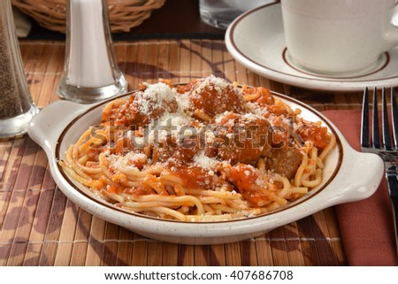 A bowl of spaghetti and meatballs with parmesan cheese - stock photo