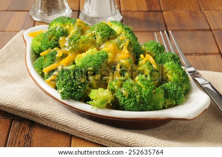 A bowl of steamed broccoli topped with cheddar cheese - stock photo