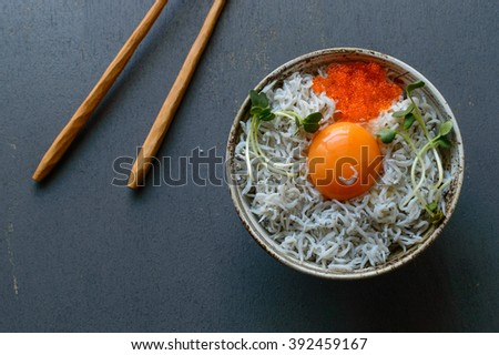 a bowl of steamed rice topped with small sardines, an egg Yolk, flying fish roes and garnished with kaiware sprouts