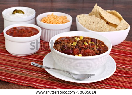 A bowl of taco soup surrounded with condiments including sour cream, salsa, tortilla chips and shredded cheddar cheese. - stock photo