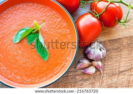 A bowl of tomato soup gaspacho with basil, tomatoes and garlic - stock photo
