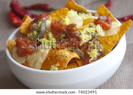 A bowl of vegetarian nachos with cheese, salsa sauce and jalapenos - stock photo