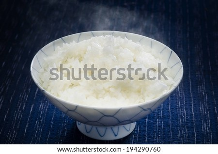 A bowl of white rice on a blue wooden table. - stock photo