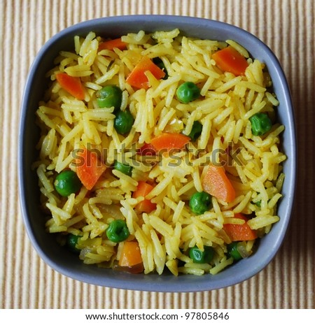A bowl of yellow basmati rice with carrots, peas, onion and curry