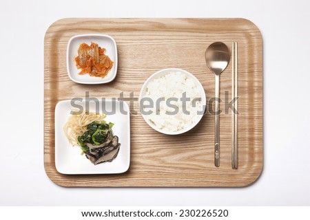A bowl with rice, A dish(plate) with vegetable food(spinach, bean sprouts, mushroom), A small dish with Kimchi, spoon, chopsticks, wood tray isolated white, top view at the studio. - stock photo