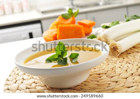 a bowl with vegetable soup and some of the ingredient to prepare it, such as pumpkin and leeks, on the countertop of a kitchen - stock photo