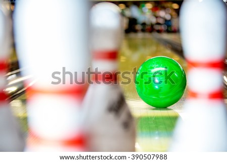 A bowling ball about to hit the pins on a 10 pin bowling alley, seen from the point of view of one of the pins - stock photo