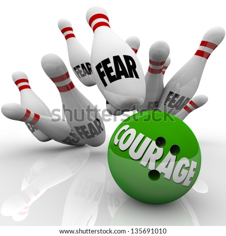A bowling ball marked Courage strikes pins with the word Fear to symbolize bravery and courageous action to overcome obstacles you're afraid of - stock photo