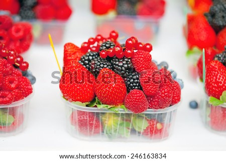 A box of bright fresh berries on a market stall - stock photo