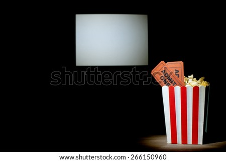 A box of popcorn with two tickets on white background screen cinema  - stock photo