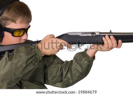 A boy aims his rifle.  He is properly dressed wearing eye and hearing protection.
