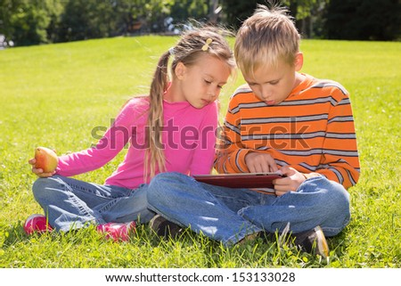 A boy and a girl are looking at the screen of a tablet computer while lying on a green lawn - stock photo