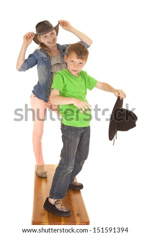 A boy and a girl holding on to cowboy hats with a smile. - stock photo