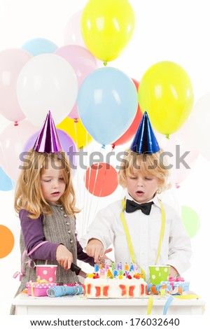 A boy and a girl in party hats with a cake.