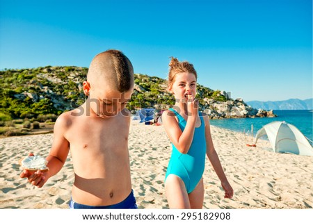 A boy and a girl on the beach eating sandwiches on the go.