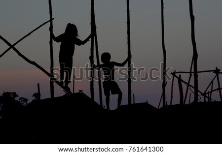 A boy and a girl play on wooden poles sunk into Tonle Sap lake, Cambodia. The shacks along the lake are supported on wooden poles or stilts.