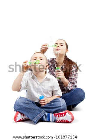 A boy and a woman sit cross-legged on the floor and let go soap bubbles. - stock photo