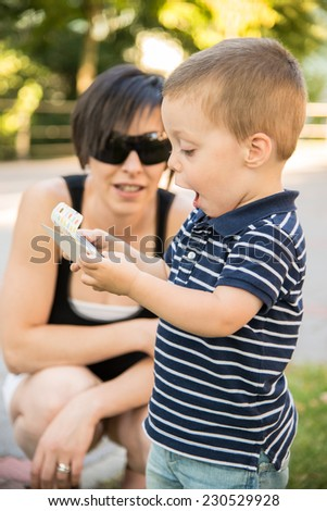 a boy and a young woman playing with a smartphone - stock photo