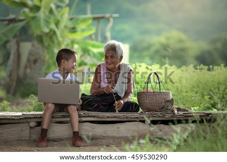 A boy and grandmother with a laptop at cottage - stock photo