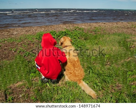 A boy and his dog sit by the water's edge and wish they could go swimming - stock photo