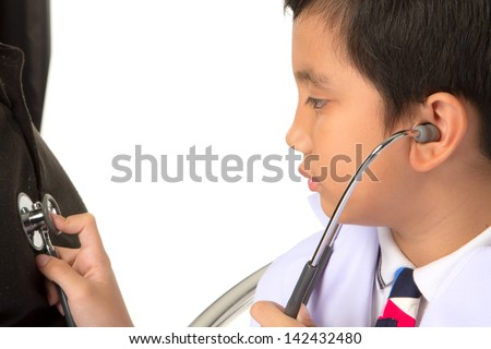 A boy as doctor examining a man - stock photo