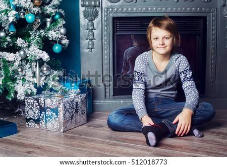 a boy at home with the Christmas tree and presents