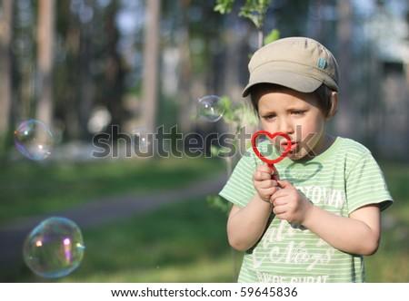 A boy blowing bubbles - stock photo