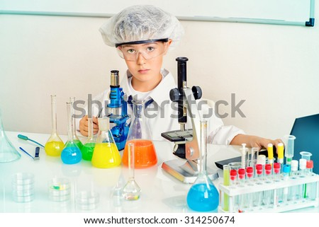 A boy concentrated working in the laboratory. Science and education. School. - stock photo