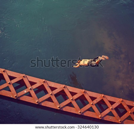 a boy diving  off an old train trestle bridge into a river toned with a retro vintage instagram filter effect - stock photo