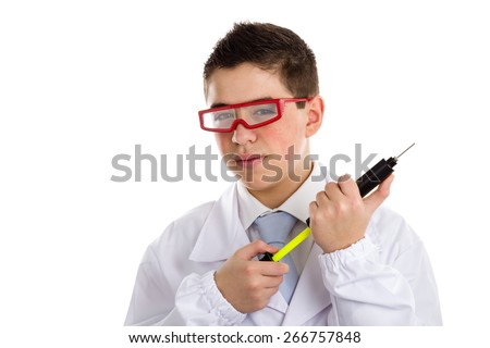 A boy doctor with acne skin in white coat wearing red googles and holding a black pump syringe helps to feel medicine more friendly - stock photo