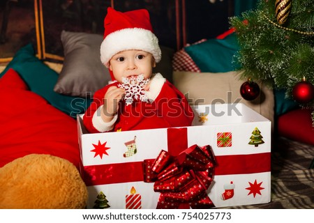 A boy dressed as Santa Claus. In the gift box near the Christmas tree. Christmas and children. New Year