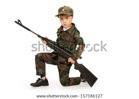 A boy dressed like a soldier standing with a rifle. Different occupations. Isolated over white.