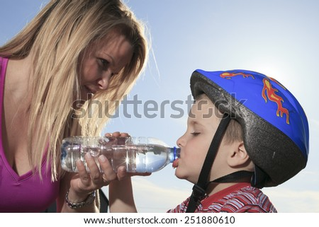 A boy drinking water outside with sky on the background. - stock photo