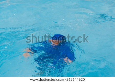 A boy drowning in the blue pool.