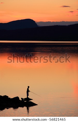 A boy fishing in a lake in the mountains