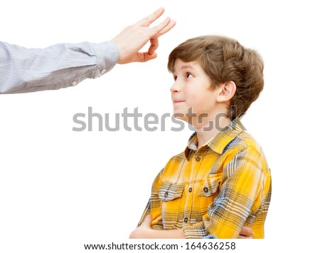 a boy gets a click in the forehead of the parent - stock photo