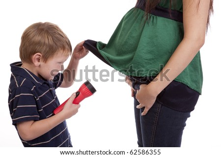 A boy has a flashlight and is looking under his pregnant moms shirt.