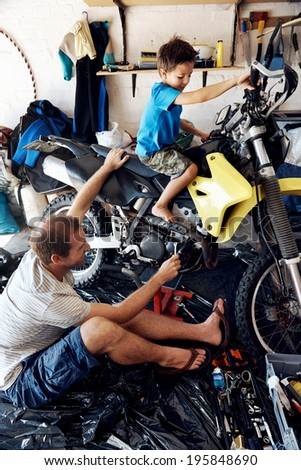 A boy helping his dad with fixing a motorcycle in the garage - stock photo