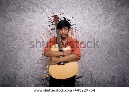 A boy hold his guitar - stock photo