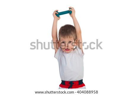 A boy holding a dumbbell with both hands over his head - stock photo