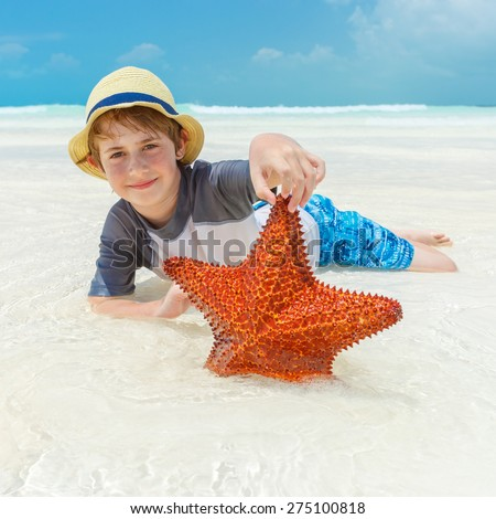 A Boy holding a starfish on a tropical beach in Cayo Largo - stock photo